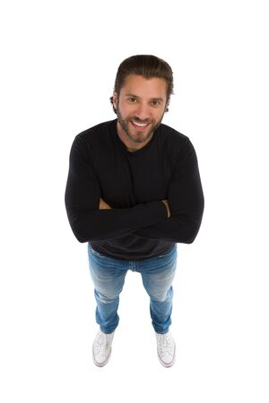Young smiling man standing with arms crossed and looking up. High angle view. Full length studio shot isolated on white.