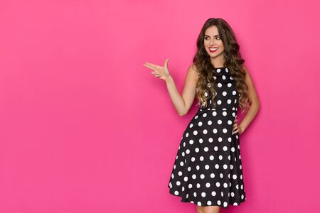 Beautiful young woman in black cocktail dress is looking away, smiling and aiming with two fingers. Three quarter length studio shot on pink background.