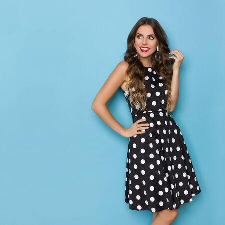 Pretty young woman in black cocktail dress in polka dots pattern is holding hand on hip, looking away and smiling. Three quarter length studio shot on blue background.
