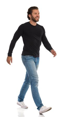 Smiling young man in jeans, sneakers and black jersey is walking and looking away. Side view. Full length studio shot isolated on white.