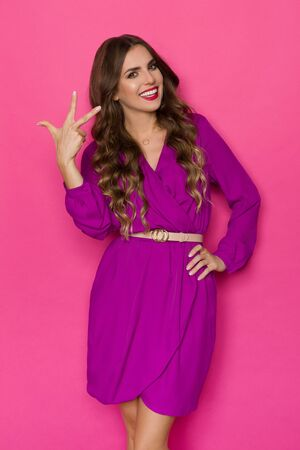 Beautiful young woman in elegant purple dress is showing three fingers and smiling. Three quarter length studio shot on pink background.