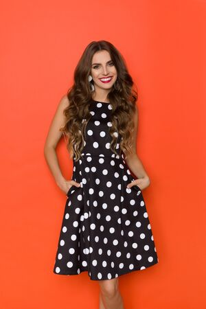 Cute young woman in elegant black cocktail dress in polka dots pattern is looking at camera, holding hands in pockets and smiling. Three quarter length studio shot on orange background.