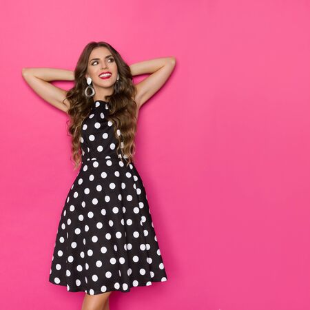 Curious beautiful young woman in black cocktail dress in polka dots is standing, holding hands behind head, looking away. Three quarter length studio shot on pink background.