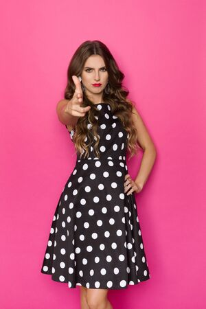 Confident young woman in black cocktail dress is aiming with two fingers at camera. Three quarter length studio shot on pink background. Banco de Imagens