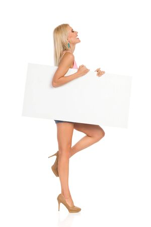 Young woman is standing on one leg, holding white poster under her arm and laughing. Side view. Full length studio shot isolated on white. Banco de Imagens