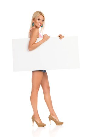 Young woman is standing, holding white poster under her arm and looking at camera. Side view. Full length studio shot isolated on white.