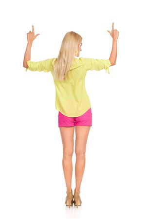 Blond woman in pink shorts, yellow shirt and high heels is standing with arms outstretched and pointing up. Rear view. Full length studio shot isolated on white. Banco de Imagens