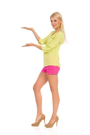Beautiful blond woman in pink shorts, yellow shirt and high heels is standing with hands raised and presenting something. Side view. Full length studio shot isolated on white.