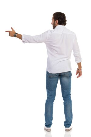 Handsome man in jeans, sneakres and white shirt is standing and pointing at side. Rear view. Full length studio shot isolated on white.