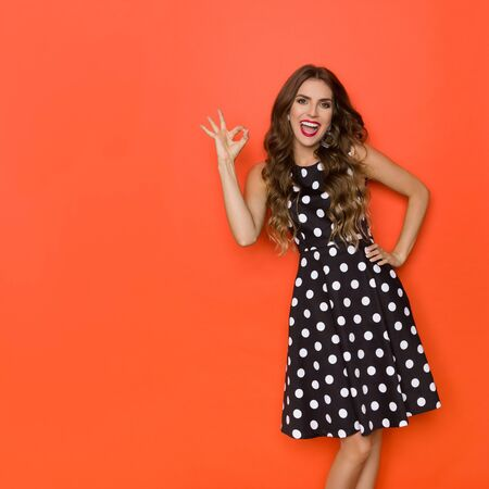 Beautiful young woman in elegant black cocktail dress in polka dots pattern is looking at camera, laughing and showing ok hand sign. Three quarter length studio shot on orange background. Banco de Imagens