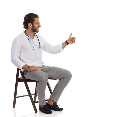 Smiling handsome male doctor is sitting on a chair, looking away and showing thumb up. Full length studio shot isolated on white. Imagens