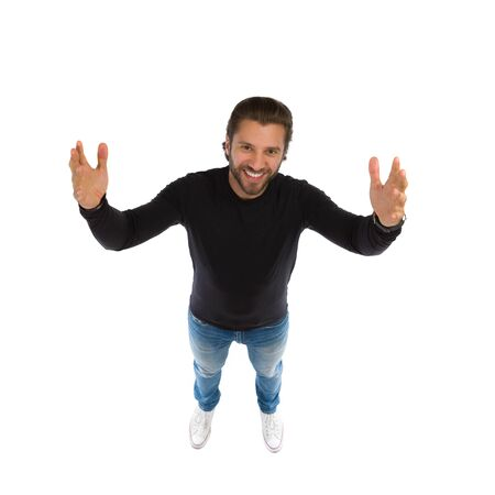 Young smiling man standing with arms outstretched and looking up. High angle view. Full length studio shot isolated on white.