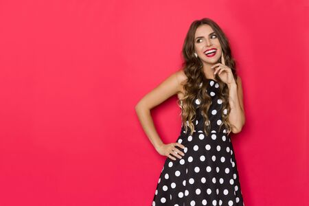 Elegant young woman in black cocktail dress in polka dots pattern is holding hand on chin, looking away and laughing. Three quarter length studio shot on red background. Banco de Imagens