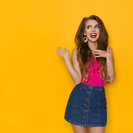 Excited young woman in jeans mini skirt and pink top is holding hand on chest, looking away and gesturing. Three quarter length studio shot on yellow background.