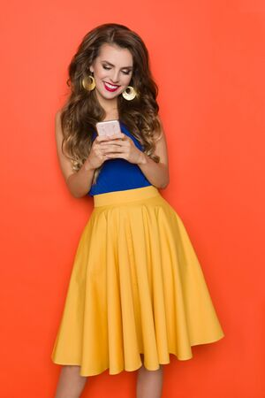 Beautiful young woman in yellow skirt and blue top is holding telephone, looking at it and smiling. Three quarter length studio shot on orange background. Banco de Imagens