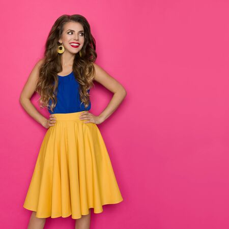 Cute young woman in yellow skirt and blue top is holding hands on hip, looking away and smiling. Three quarter length studio shot on pink background.