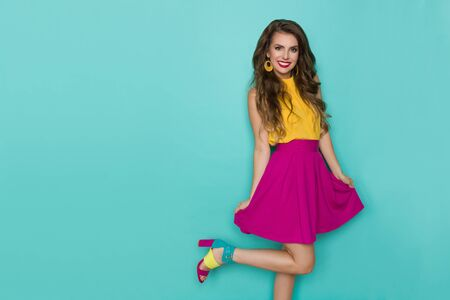 Cute young woman in vibrant clothes and high heels is standing on one leg, smiling and looking at camera. Three quarter length studio shot on turquoise background.