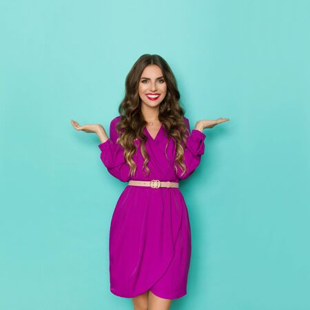 Beautiful young woman in purple dress is holding hands raised, looking at camera and smiling. Three quarter length studio shot on turquoise background.