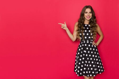 Beautiful young woman in black cocktail dress is pointing at side, looking at camera and smiling. Three quarter length studio shot on red background.