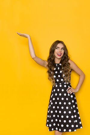 Beautiful young woman in black cocktail dress in polka dots pattern is standing with hand raised, presenting something and looking up. Three quarter length studio shot on yellow background.