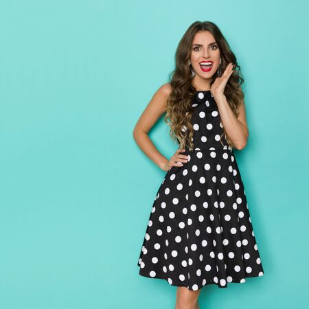 Excited and happy young woman in black cocktail dress in polka dot pattern is holding hand on chin, looking at camera and talking. Three quarter length studio shot on turquoise background.