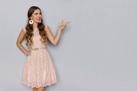 Young beautiful woman in elegant beige lace mini dress is looking away, smiling and pointing. Three quarter length studio shot on gray background.