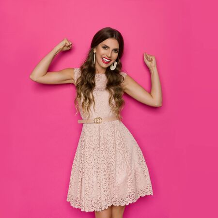 Confident young woman in elegant beige lace cocktail dress is standing with arm raised, flexing muscles and smiling. Three quarter length studio shot on pink background.