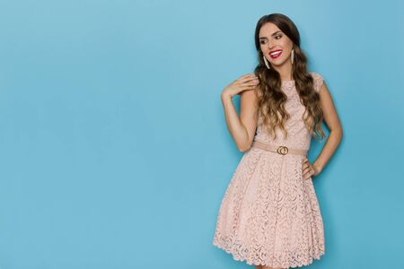 Happy beautiful young woman in beige lace mini dress is holding hand on shoulder, looking away and smiling. Three quarter length studio shot on blue background.