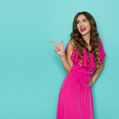 Beautiful young woman in elegant pink dress is pointing at copy space and looking away over shoulder and laughing. Three quarter length studio shot on turquoise background.