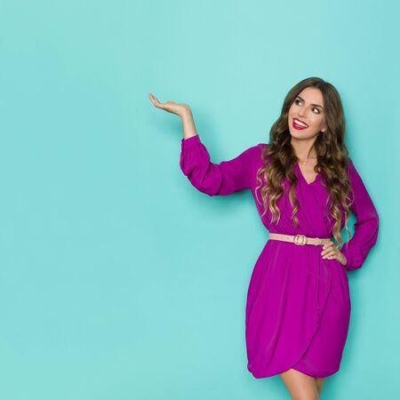 Beautiful young woman in purple dress is holding hand raised, looking at it and smiling. Three quarter length studio shot on turquoise background.