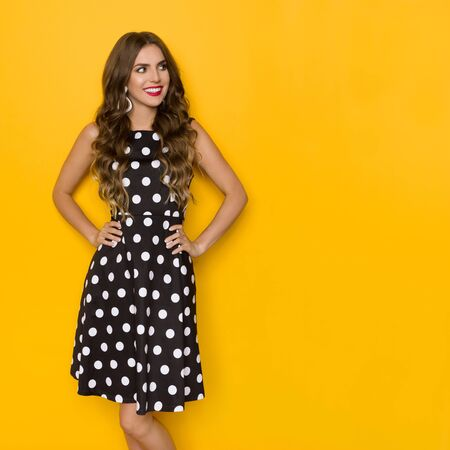 Pretty young woman in black cocktail dress in polka dots is posing with hands on hip, looking away and smiling. Three quarter length studio shot on yellow background.