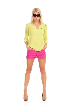 Beautiful blond woman in sunglasses, pink shorts, yellow shirt and high heels is standing with hands in pockets and looking at camera. Front view. Full length studio shot isolated on white. Banco de Imagens