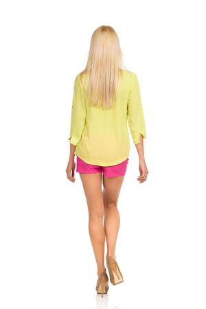 Rear view of blond woman walking in pink shorts, green shirt and high heels. Full length studio shot isolated on white. Banco de Imagens