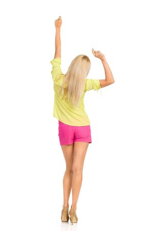 Rear view of dancing blond woman in pink shorts, green shirt and high heels. Full length studio shot isolated on white.