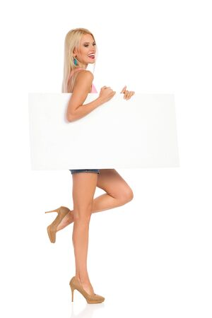 Young woman is walking, holding white poster under her arm and laughing. Side view. Full length studio shot isolated on white.