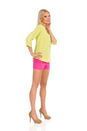 Beautiful blond woman in pink shorts, yellow shirt and high heels is standing, looking at camera, cholding hand on chin and smiling. Full length studio shot isolated on white. Banco de Imagens