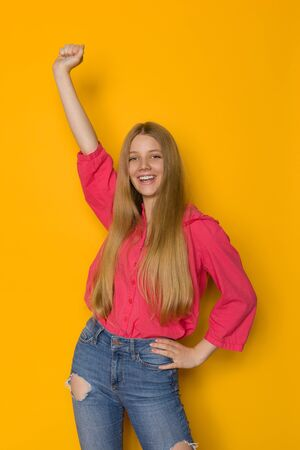 Happy teen girl in jeans and red shirt is standing with arm raised and shouting. Three quarter length studio shot on yellow background.
