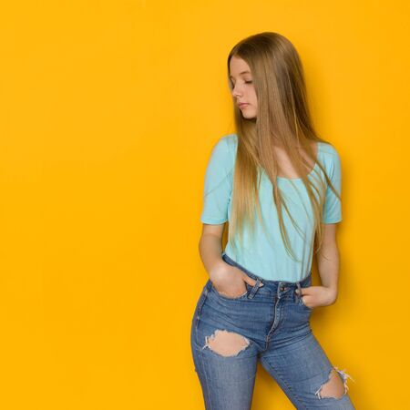 Beautiufl teen girl in jeans and turquoise shirt is standing with hands in pocket and looking away. Three quarter length studio shot on yellow background. Banco de Imagens