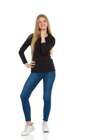 Teenage girl in jeans, sneakers and black blouse is standing, holding hand on chin, looking away and smiling. Front view. Full length studio shot isolated on white.
