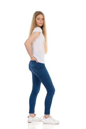 Teenage girl in jeans, sneakers and white shirt is standing with hand in pocket and looking at camera. Side view. Full length studio shot isolated on white.