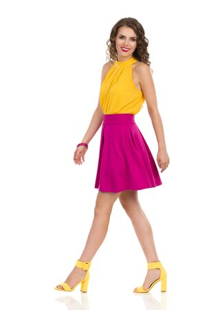 Beautiful young woman in yellow high heels and pink mini skirt is walking, looking at camera and smiling. Side view. Full length studio shot isolated on white.