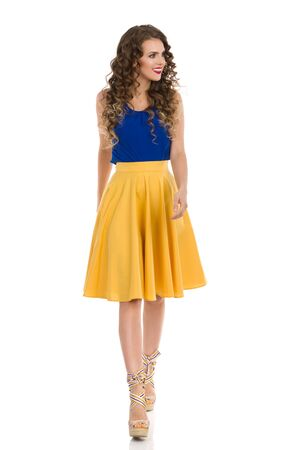 Beautiful young woman in yellow skirt, blue topa and wedges is walking, looking away and smiling. Front view. Full length studio shot isolated on white.