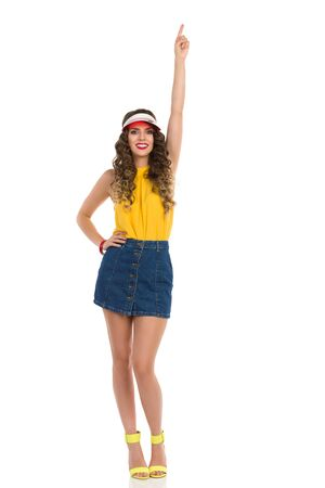 Confident young woman in jeans mini skirt, yellow top and high heels is standing with arm raised and pointing up. Full length studio shot isolated on white.