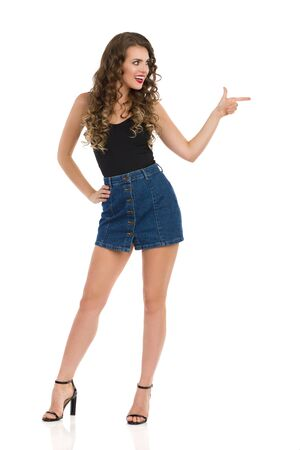 Confident young woman in jeans mini skirt, black top and high heels is standing legs apart, looking away, pointing and talking. Full length studio shot isolated on white.
