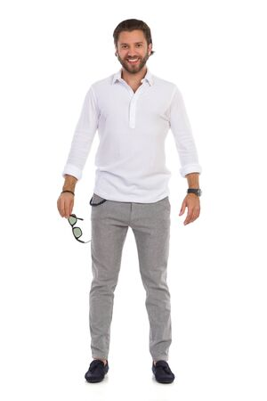 Smiling young man in moccasins, gray trusers, and white shirt is standing, holding sunglasses, smiling and looking at camera. Full length studio shot isolated on white. Banco de Imagens