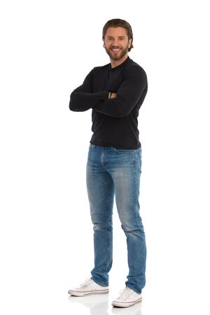 Smiling young man in jeans, sneakers and black jersey is standing with arms crossed and looking at camera. Full length studio shot isolated on white.