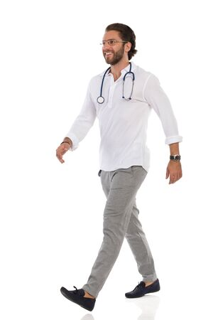 Smiling handsome male doctor is walking and looking away. Side view. Full length studio shot isolated on white.