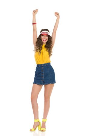 Happy young woman in jeans mini skirt, yellow top and high heels is standing with arms raised and cheering. Full length studio shot isolated on white.