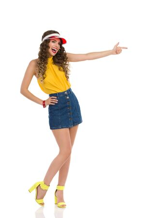 Beautiful young woman in jeans mini skirt, yellow top and high heels is pointing and laughing. Full length studio shot isolated on white.