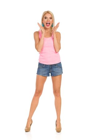 Beautiful blond woman in jeans shorts, pink tank top and high heels is standing, holding hands raised, shouting and looking at camera. Front view. Isolated On White. Stock Photo